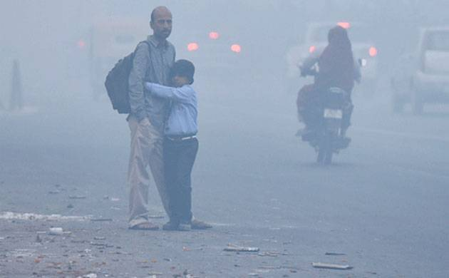 A student awaits his school bus on a smoggy morning in Delhi. (Getty Images)