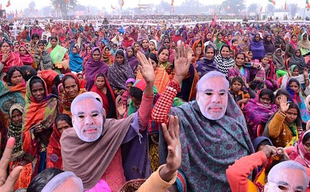 BJP supporters listen to Prime Minister Narendra Modi as he delivers a speech through mobile phone during a Parivartan rally in Bahraich. (File Photo: Getty Images)