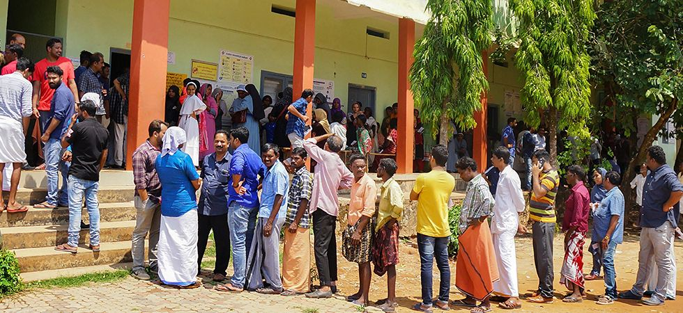 People wait in long queues to cast their votes at a polling station at Batheri in Wayanad