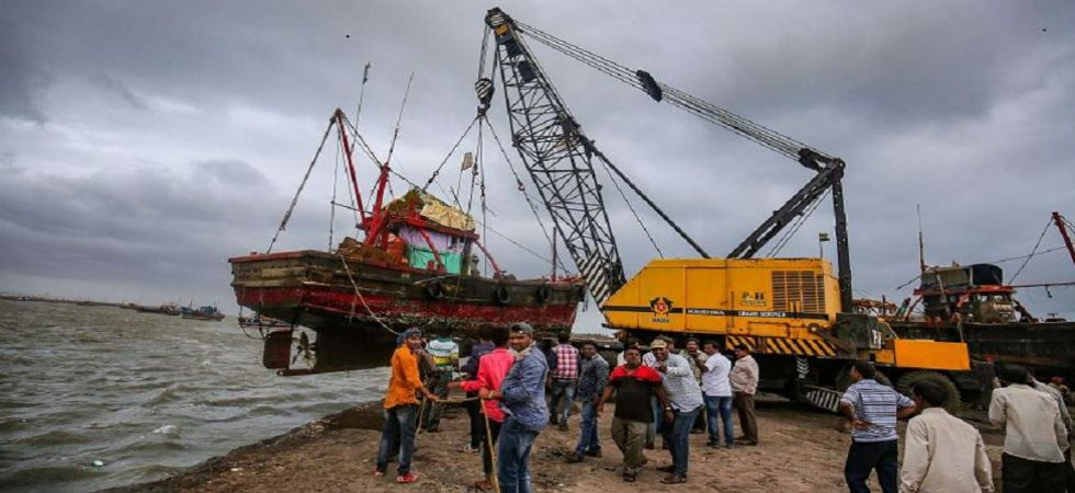 A crane lifts a boat from the shore to move it to a safer place ahead of the landfall of Cyclone Vayu (Photo Source: PTI)