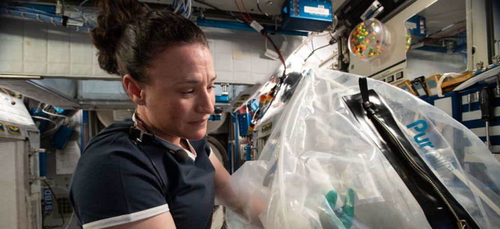 Astronaut Serena M Aunón-Chancellor conducts the Microgravity Investigation of Cement Solidification experiment using the new Portable Glovebag. (Photo credit: NASA)