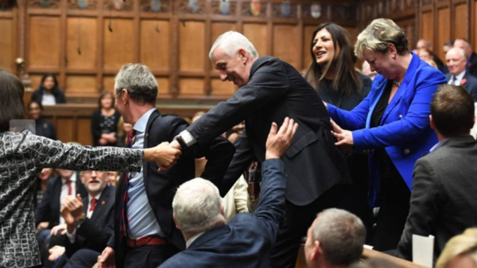 Lindsay Hoyle being dragged to the speaker's elevated green chair